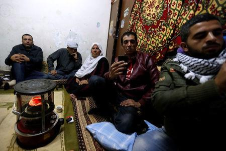 A Palestinian refugee family watches a televised broadcast of U.S. President Donald Trump delivering an address where he is expected to announce that the United States recognises Jerusalem as the capital of Israel, at Al-Baqaa Palestinian refugee camp, near Amman, Jordan December 6, 2017. REUTERS/Muhammad Hamed