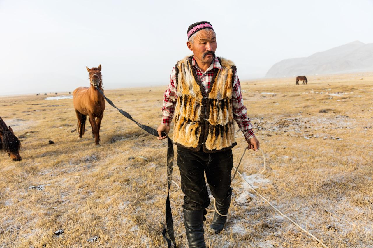"""Early one morning I joined Dalaikhan as he was rounding up his horses to get ready for the trek to Ulgii for the eagle festival. The waistcoat he's wearing is very commonly worn among the eagle hunters, and is made with the fur of a fox he caught with his eagle. While he was born in Mongolia, his family is from Kazakhstan—in fact, eagle hunting is originally a Kazakh tradition, which is why so much of it is practiced in western Mongolia, right near the border."""