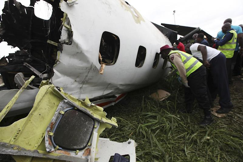Rescue workers peer into the wreckage of a charter passenger jet which crashed soon after take off from Lagos airport, Nigeria, Thursday, Oct. 3, 2013. Officials said there were casualties but refused to confirm reports of several deaths. (AP Photo/Sunday Alamba)