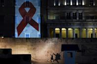 The Greek parliament is illuminated with the Red Ribbon logo of HIV AIDs during the World AIDS Day on December 1, 2016