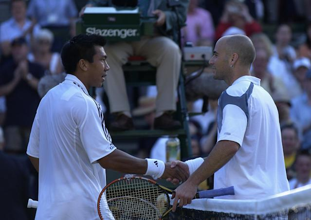 WIMBLEDON - June 26: Paradorn Srichaphan of Thailand is congratulated by Andre Agassi of the USA after his victory at the All England Tennis Championships at the All England Lawn Tennis Club, Wimbledon, England, on June 26, 2002. (Photo by Clive Brunskill/Getty Images)