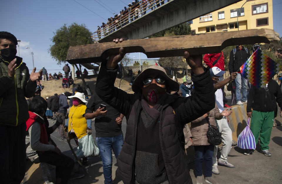 Demonstrators wearing face masks amid the COVID-19 pandemic protest the postponement of the upcoming presidential election in El Alto, Bolivia, Monday, Aug. 10, 2020. Citing the ongoing new coronavirus pandemic, the nation's highest electoral authority delayed presidential elections from Sept. 6 to Oct. 18, the third time the vote has been delayed. (AP Photo/Juan Karita)