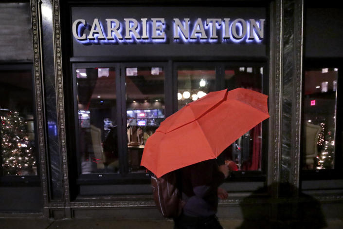 In this Dec. 10, 2019, file photo a woman holding an umbrella passes the Carrie Nation lounge in Boston, titled after the namesake of the woman supporting the temperance movement prior to the 1920 Prohibition ban on alcohol. (AP Photo/Charles Krupa, File)