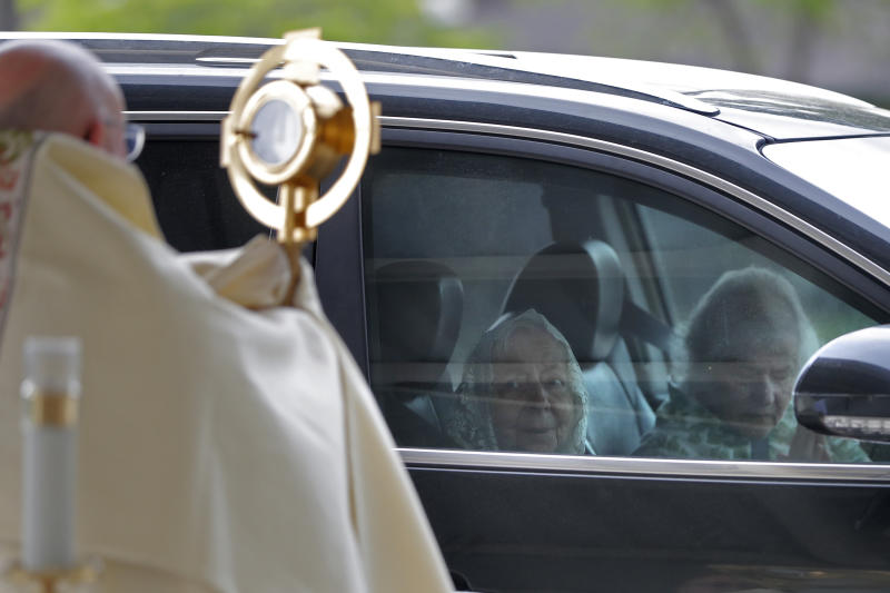 Parishioners pray from their car as Fr. Steve Buno, Pastor of St. Rita of Cascia Catholic Church in Harahan, La., performs drive-thru Benediction of the Blessed Sacrament, as a form of social distancing due to the new coronavirus, during Holy Week, Tuesday, April 7, 2020. (AP Photo/Gerald Herbert)