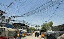 Iraqis walk under a labyrinth of cables linking homes to private electric generators in Baghdad's Sadr City