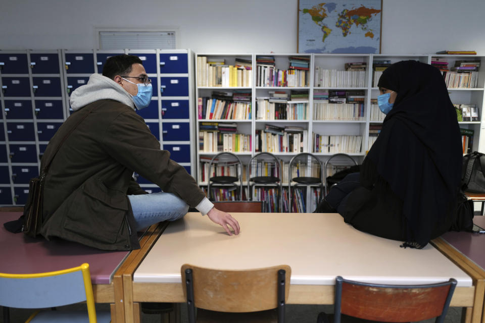 Zinedine Gaid, teacher of economy sciences and philosophy, left, talks with Rafika, last name withheld, a student mother, at the MHS, Meo High School private college, in Paris Tuesday, Feb. 9, 2021. More than three dozen police officers descended on the small private school, blocked students inside their classrooms, took photos everywhere, even inside the refrigerator, and grilled the school director in her office. Such operations illustrate French efforts to fight extremism as lawmakers prepare to vote on a bill aimed at snuffing it out. (AP Photo/Francois Mori)