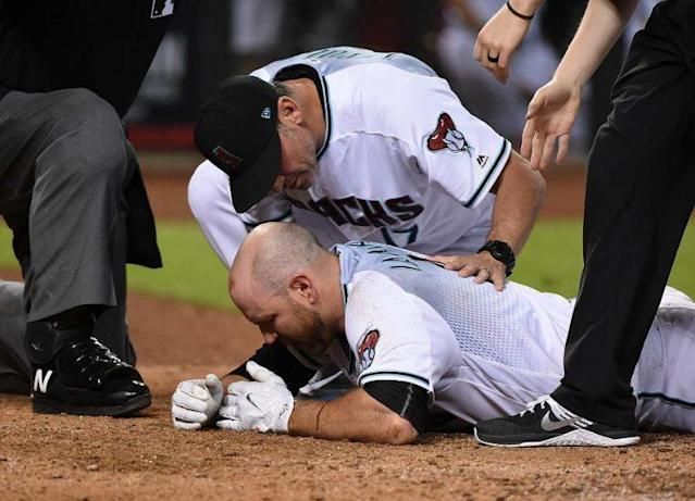 Chris Iannetta is tended to by Diamondbacks manager Torey Lovullo after getting hit in the face by a pitch on Friday night. (Getty Images)