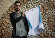 Palestinian Karam Qawasmi, who was shot in the back by Israeli forces in an incident caught on video last year, holds up the shirt he was wearing when he was shot, in the garden of his house, in the West Bank city of Hebron, Sunday, Nov. 10, 2019. In his first interview since the video emerged last week, Karam Qawasmi said he was run over by a military jeep, then beaten for several hours before troops released him, only to shoot him in the back with a painful sponge-tipped bullet as he walked away. (AP Photo/Majdi Mohammed)