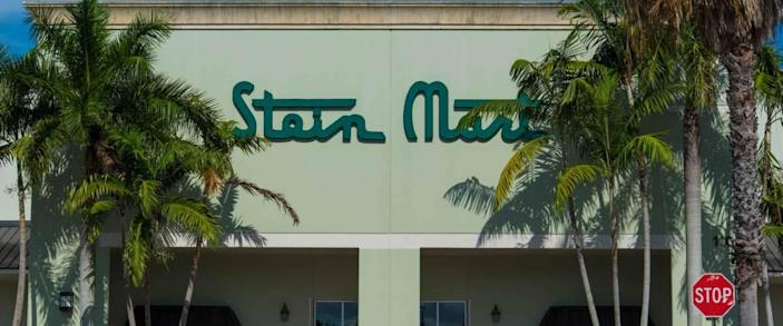 Palm Beach, FL USA 07/10/2019 Stein Mart South Florida Business Exterior with Sign Slightly Obscured By Tall Palm Trees