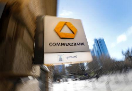 FILE PHOTO: A sign for an ATM of Commerzbank is seen next to the headquarters of Deutsche Bank (R) in Frankfurt, Germany, March 19, 2019.  REUTERS/Kai Pfaffenbach/File Photo