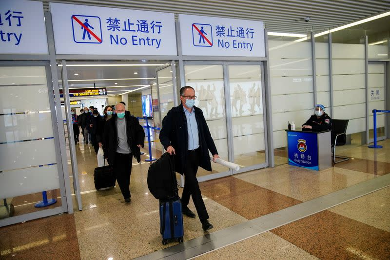 Members of the World Health Organisation (WHO) arrive at the airport in Shanghai