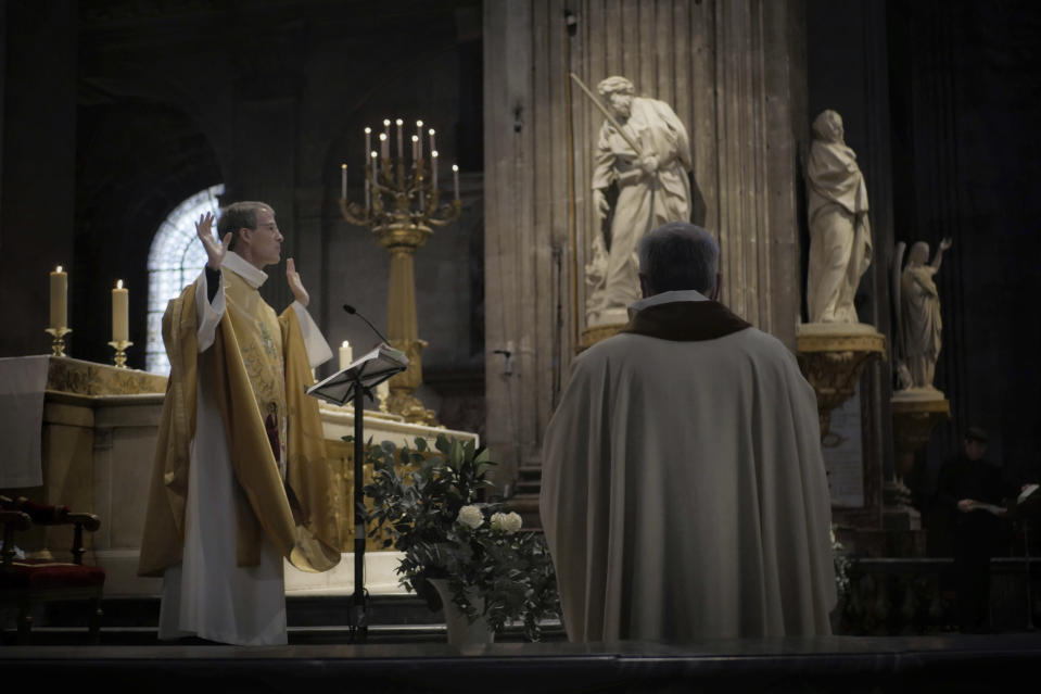 Priest Henri de La Hougue, left, celebrates the All Saints Day mass in Saint-Sulpice church, in Paris, Sunday, Nov. 1, 2020. France heightened its security alert amid religious and geopolitical tensions around cartoons mocking the Muslim prophet. (AP Photo/Thibault Camus)