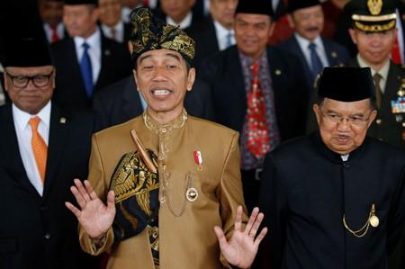 Indonesia's President Joko Widodo and Vice President Jusuf Kalla react to reporters after the president addressed them ahead of Independence Day at the parliament building in Jakarta