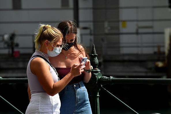 Two young women in face masks walk along a quiet Circular Quay in Sydney.