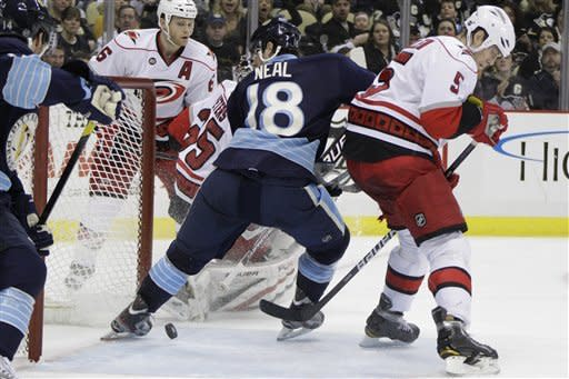Pittsburgh Penguins' James Neal (18) tips in a second-period goal behind Carolina Hurricanes' Bryan Allen (5) and goalie Justin Peters during an NHL hockey game in Pittsburgh on Tuesday, Dec. 27, 2011. (AP Photo/Gene J. Puskar)