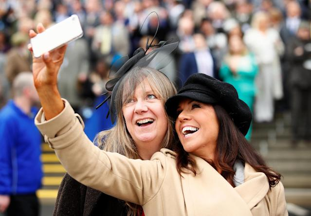 Horse Racing - Grand National Festival - Aintree Racecourse, Liverpool, Britain - April 13, 2018 Racegoers pose for a selfie during Ladies Day at the Grand National Festival Action Images via Reuters/Jason Cairnduff