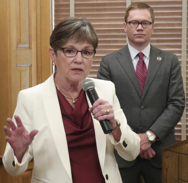 """Kansas Gov. Laura Kelly answers questions from reporters after signing her executive order aimed at ending an economic """"border war"""" between her state and Missouri over jobs in the Kansas City area, Friday, Aug. 2, 2019, at the Statehouse in Topeka, Kansas. Standing behind her is Kansas Commerce Secretary David Toland. (AP Photo/John Hanna)"""