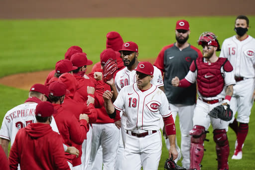 Cincinnati Reds celebrate after defeating the Pittsburgh Pirates 4-1 in a baseball game in Cincinnati, Tuesday, Sept. 15, 2020. (AP Photo/Bryan Woolston)