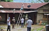 Forest official try to rescued a tigress which strayed into a house in Baghmari area at Bagori range being rescued in Nagaon District of Assam. (Photo credit should read Anuwar Ali Hazarika/Barcroft Media via Getty Images)