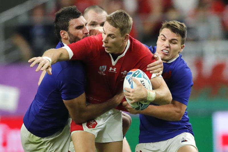 Wales' Liam Williams, center, is tackled by France's Antoine Dupont, right, during the Rugby World Cup quarterfinal match at Oita Stadium in Oita, Japan, Sunday, Oct. 20, 2019. (AP Photo/Christophe Ena)