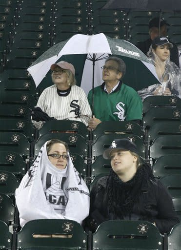 Chicago White Sox fans sit under an umbrella and watch a live broadcast of the Bears Green Bay Packers game on the big screen during the rain delay of a baseball game between the White Sox and the Detroit Tigers Thursday, Sept. 13, 2012, in Chicago. (AP Photo/Charles Rex Arbogast)
