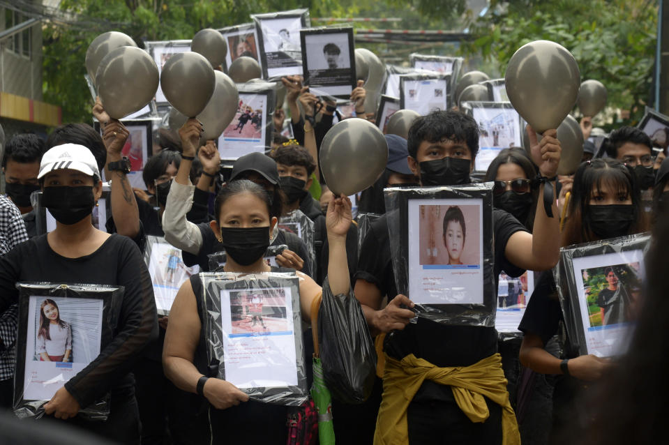 Anti-coup protesters holding pictures of those who died during a protest against the military offer prayers for them, in Yangon, Myanmar, Monday, April 5, 2021. Threats of lethal violence and arrests of protesters have failed to suppress daily demonstrations across Myanmar demanding the military step down and reinstate the democratically elected government. (AP Photo)
