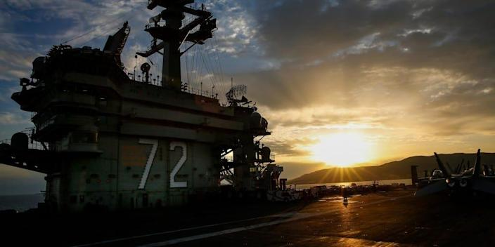 The sun sets as the Nimitz-class aircraft carrier USS Abraham Lincoln (CVN 72) is anchored off the coast of Palma de Mallorca, Spain.