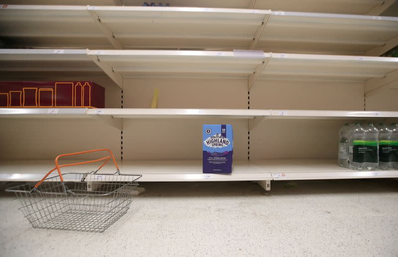A shopping basket is discarded next to empty shelves of the soft drinks aisle, in Sainsbury's supermarket in Harpenden