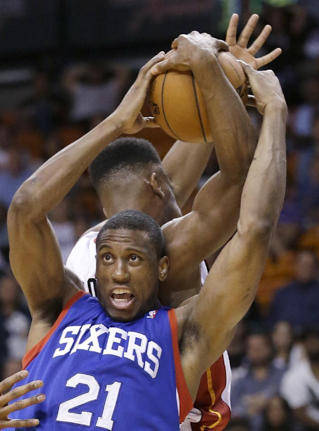 Philadelphia 76ers forward Thaddeus Young (21) and Miami Heat guard Norris Cole, rear, battle for the ball during the second half of an NBA basketball game on Wednesday, April 16, 2014, in Miami. The 76ers defeated the Heat 100-87. (AP Photo/Wilfredo Lee)
