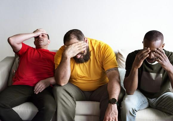 Three men on a sofa looking distressed.