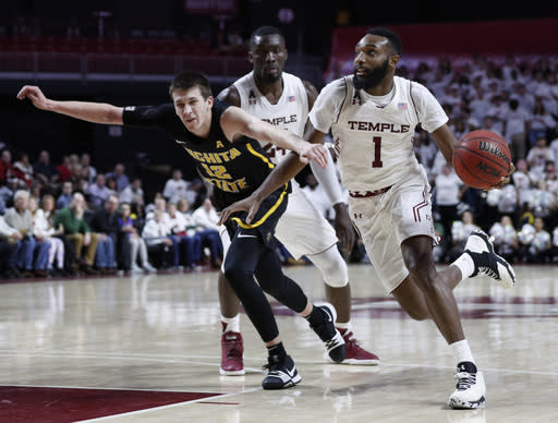 "Temple's <a class=""link rapid-noclick-resp"" href=""/ncaaf/players/263348/"" data-ylk=""slk:Josh Brown"">Josh Brown</a>, right, drives to the basket against Wichita State's <a class=""link rapid-noclick-resp"" href=""/ncaab/players/136718/"" data-ylk=""slk:Austin Reaves"">Austin Reaves</a>, left, during the second half of an NCAA basketball game, Thursday, Feb. 1, 2018, in Philadelphia. Temple won 81-79 in overtime. (AP Photo/Chris Szagola)"