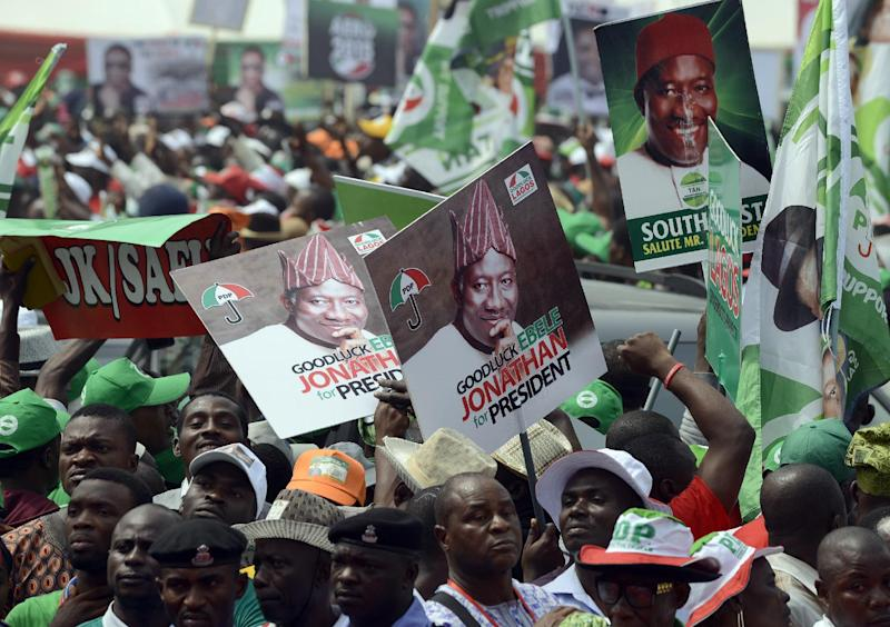 Party supporters raise flags in support of Nigerian President and presidential candidate Goodluck Jonathan during a rally in Lagos on January 8, 2015