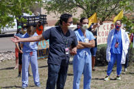 In this May 8, 2020, photo, medical staff from Rehoboth McKinley Christian Hospital including Caleb Lauber, center, hold a protest over working conditions and depleted staff in Gallup, N.M. Many nurses and doctors say staffing at the hospital was inadequate because of hospital CEO David Conejo's move to cut back on nurses in the first week of March to offset declining hospital revenues after elective surgeries were suspended. They voiced their discontent at the recent protest calling for his resignation. (AP Photo/Morgan Lee)