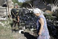A woman cries as a Ukrainian serviceman looks at her ruined house in Pervomayskiy, some 5km northwest of Donetsk, eastern Ukraine, on September 6, 2014 (AFP Photo/Anatolii Stepanov)