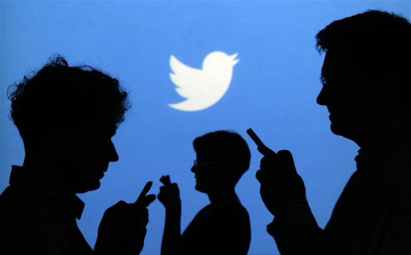 File picture illustration shows people holding mobile phones silhouetted against a backdrop on which the Twitter logo is projected, in Warsaw