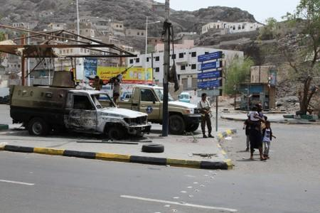 People walk past military vehicles that were burned during clashes in Aden