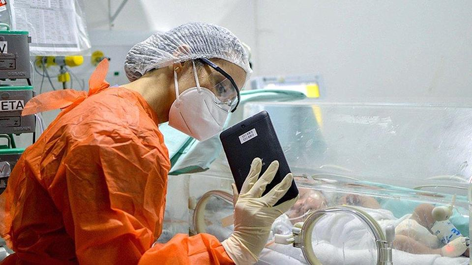 A doctor holds up a tablet to a child in ICU