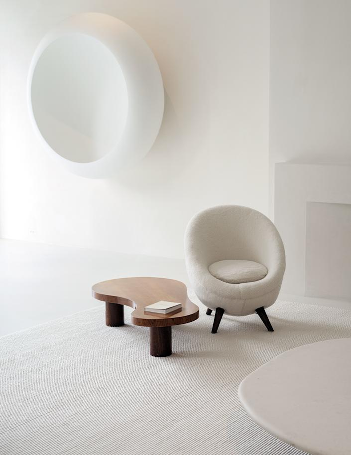 "<div class=""caption""> A Jean Royère chair and table in the living room. On wall, Anish Kapoor fiberglass sculpture. </div>"