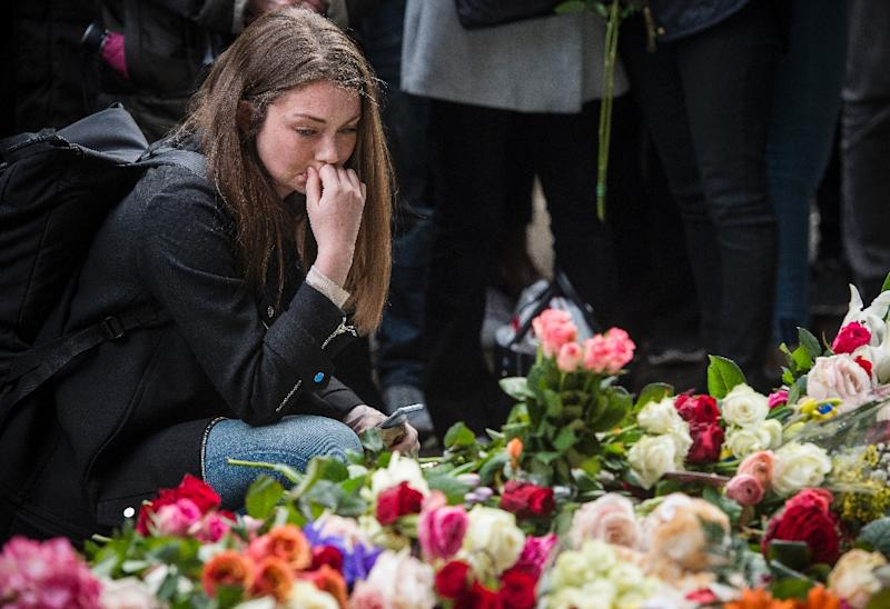 A woman reacts during a minute of silence to commemorate the victims of Friday's terror attack at a makeshift memorial near the site where a truck drove into Ahlens department store in Stockholm, Sweden, on April 10, 2017 (AFP Photo/Jonathan NACKSTRAND)