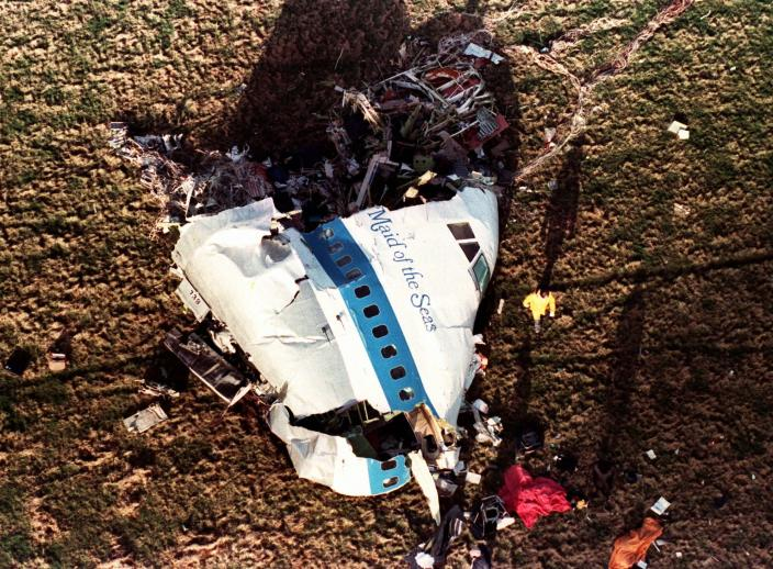 FILE - In this Dec. 22, 1988, file photo police and investigators look at what remains of the nose of Pan Am 103 in a field in Lockerbie, Scotland. The Justice Department expects to unseal charges in the coming days in connection with the 1988 bombing of a Pan Am jet that exploded over Lockerbie, Scotland, killing 270 people, according to a person familiar with the case. (AP Photo/Martin Cleaver, File)