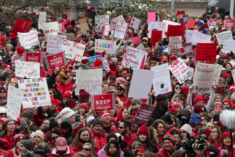 Thousands of Indiana teachers wearing red surround the Statehouse in Indianapolis, Tuesday, Nov. 19, 2019 for a rally calling for further increasing teacher pay in the biggest such protest in the state amid a wave of educator activism across the country. Teacher unions says about half of Indiana's nearly 300 school districts are closed while their teachers attend Tuesday's rally while legislators gather for 2020 session organization meetings.(AP Photo/Michael Conroy)