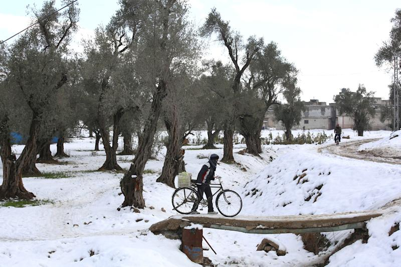 A Syrian man walks with his bicycle on a small bridge in the city of Douma, a day after a major winter storm hit the region on January 8, 2015