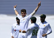 Pakistan bowler Shaheen Afridi celebrates with teammates after taking the early wicket of New Zealand's Tom Latham on day one of the first cricket test between Pakistan and New Zealand at Bay Oval, Mount Maunganui, New Zealand, Saturday, Dec. 26, 2020. (Andrew Cornaga/Photosport via AP)
