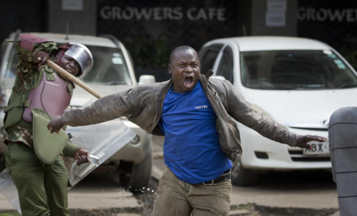 An opposition supporter yells as he is beaten with a wooden club by riot police while trying to flee during a protest in downtown Nairobi, Kenya, May 16, 2016. Kenyan police have tear-gassed and beaten opposition supporters during a protest demanding the disbandment of the electoral authority over alleged bias and corruption. (AP Photo/Ben Curtis)