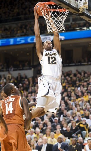 Missouri's Marcus Denmon, right, dunks the ball over Texas' J'Covan Brown, left, during the second half of an NCAA college basketball game Saturday, Jan. 14, 2012, in Columbia, Mo. Missouri won the game 84-73. (AP Photo/L.G. Patterson)