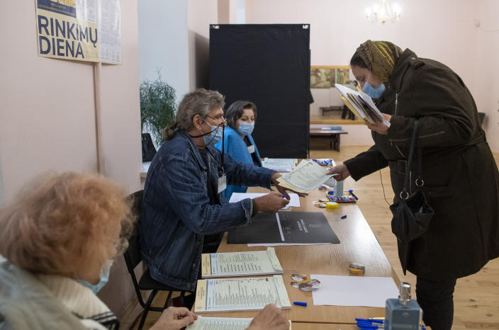 A Lithuanian woman, wearing face mask to protect against coronavirus, arrives at a polling station during parliamentary elections in Vilnius, Lithuania, Sunday, Oct.11, 2020. Polls opened Sunday for the first round of national election in Lithuania, where voters will renew the 141-seat parliament and the ruling four-party coalition is widely expected to face a stiff challenge from the opposition to remain in office. (AP Photo/Mindaugas Kulbis)