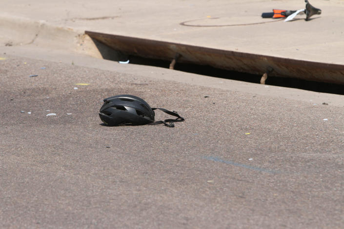 In this Saturday, June 19, 2021, photo courtesy of The White Mountain Independent a cyclist's helmet lies in the road near a damaged bike in Show Low, Ariz. A driver in a pickup truck plowed into bicyclists competing in a community road race in Arizona on Saturday, critically injuring several riders before police chased down the driver and shot him outside a nearby hardware store, police said. (Jim Headley/The White Mountain Independent via AP)