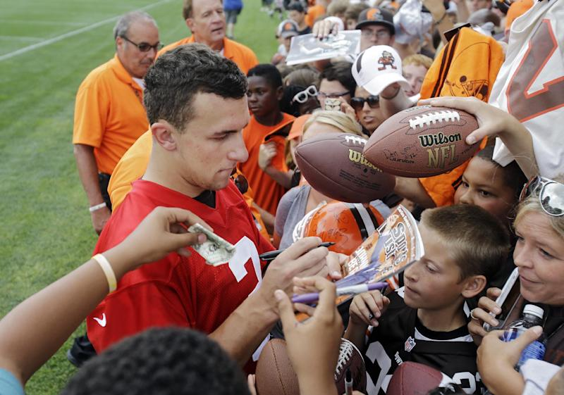 Cleveland Browns quarterback Johnny Manziel signs for fans after practice at NFL football training camp in Berea, Ohio Tuesday, Aug. 12, 2014
