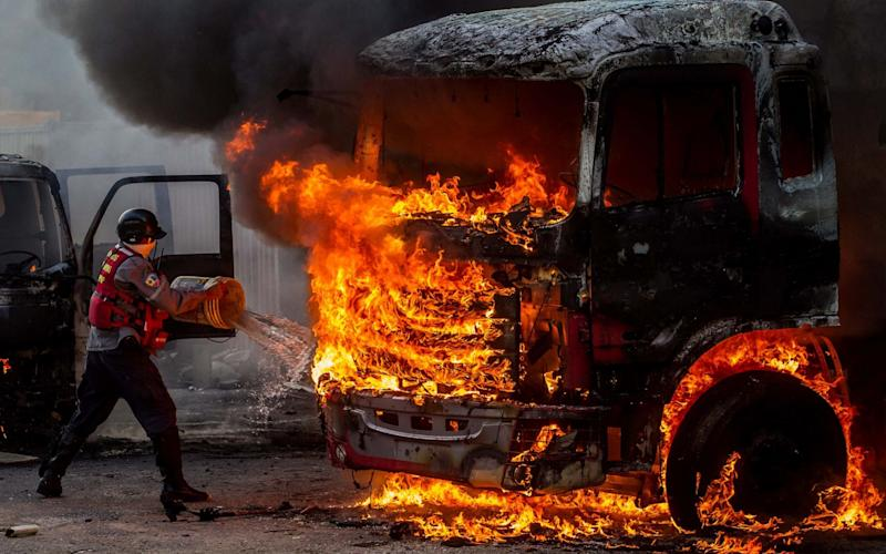 Emergency personnel try to extinguish a burning truck during a demonstration against the Venezuelan government in Caracas - EFE
