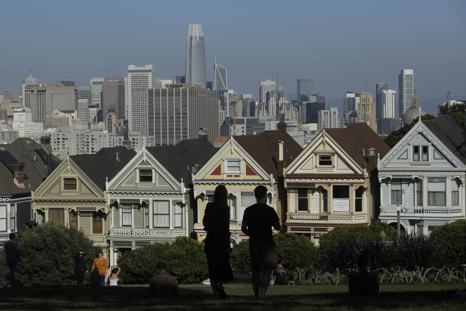 "FILE - In this Feb. 26, 2020, file photo, visitors look toward the ""Painted Ladies,"" a row of historical Victorian homes, in front of the San Francisco skyline from Alamo Square Park in San Francisco. An estimate released Friday, May 1, 2020, by the California Department of Finance said that more people are leaving California than moving in, evidence of the toll the state's housing crisis is taking as the world's fifth largest economy inches toward 40 million people. (AP Photo/Jeff Chiu, File)"